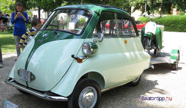 Ez is BMW, egy első ajtós Isetta 300-as, amit olasz licensz alapján 1957-ben gyártottak. A kocsi egyhengeres, négyütemű, 298 köbcentiméteres motorja 13 lóerős. Amit azért nem kevés, ha arra gondolunk, hogy a kiállításra még utánfutót is vontatott a magyar ipar egyik fontos darabjával, egy 58 kilogrammos Panni robogóval.