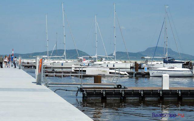 Ha már erre jártunk, megnéztük az új vitorláskikötőt. A bicikliket a parton kell hagyni, de a bal oldali mólószáron 3-400 méter besétálhattunk. Bár a kikötőt már átadták, a Balaton felőli bejáratnál még munka folyik. Még hiányoznak az úszóházak is, de hajó már van több is