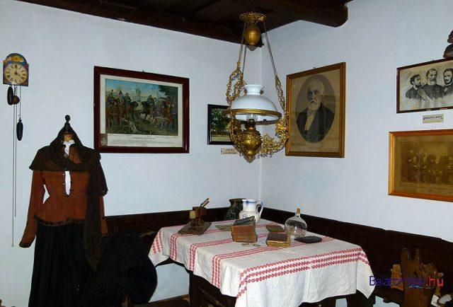Az udvari szoba jellegzetes részlete a sarokpaddal, asztallal, Lüszter-lámpával és a falon lévő történelmi polajnyomatokkal