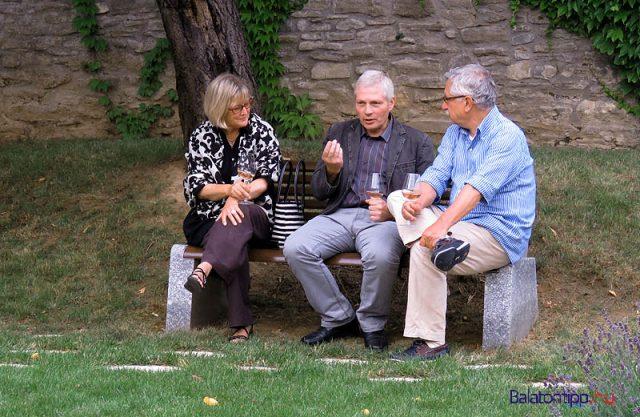 Szűcs György művészettörténész (középen), a Magyar Nemzeti Galéria főigazgató-helyettese a tavalyi Vaszary-kiállítás megnyitója után a galéria udvarán Gróf Buttler rozéval a kezében magyaráz