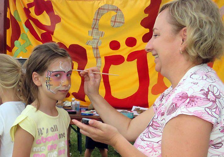Zámolyi Andrea, a keszthelyi Szemfüles Egyesület a Gyermekekért tagja éppen pillangóvá festi Zelma arcát