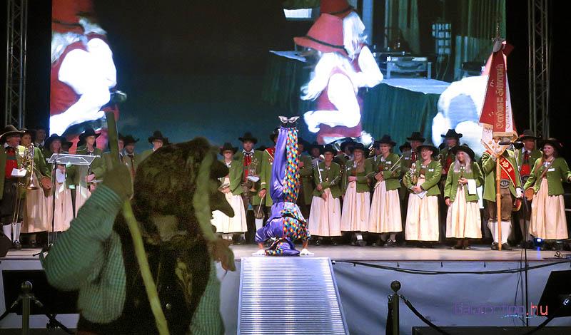A fliessi fúvósok a színpadon, az előtérben egy busószerű rém, aki társaival körbetáncolta a résztvevőket