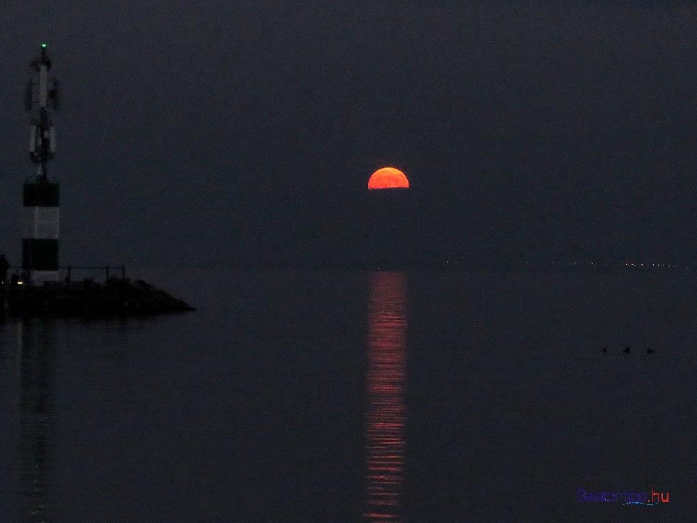 A kelő Hold a tihanyi kikötő fényoszlopával 16:51-kor