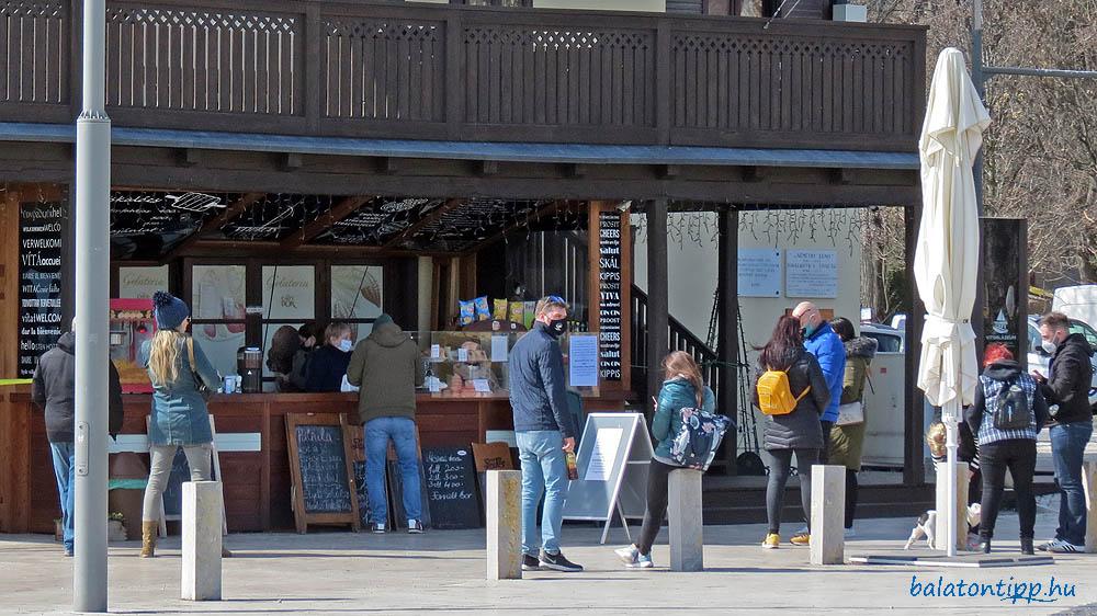 Vásárlók a Vitorlás étterem oldalában működú büfé előtt 2021. március 13-án